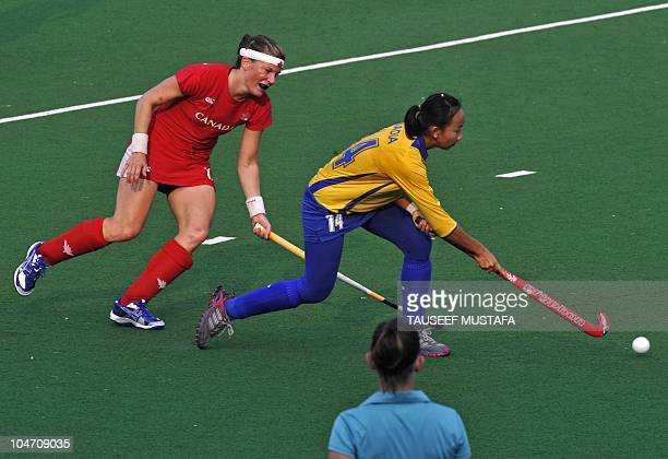Captain Stephanie Nesbit from Canada fights for the ball with captain Nadia Rahman Abdul of Malaysia during their match at the Major Dhyan Chand...