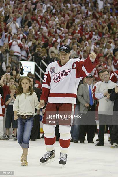 Captain Steve Yzerman of the Detroit Red Wings celebrates as he skates to center ice with his daughter Isabella for the presentation of the Stanley...