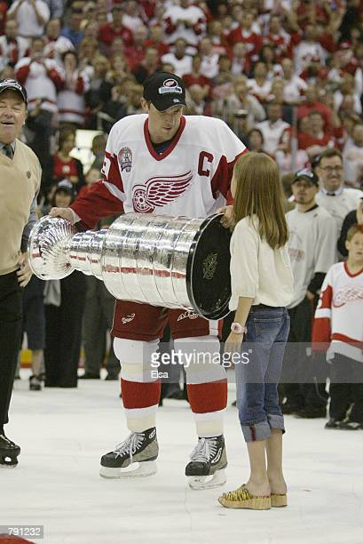 Captain Steve Yzerman of the Detroit Red Wings holds the Stanley Cup with his daughter Isabella after eliminating the Carolina Hurricanes during game...