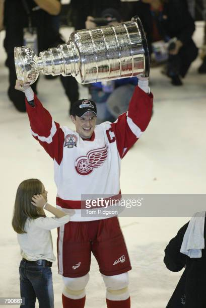 Captain Steve Yzerman of the Detroit Red Wings with his daughter Isabella raises the Stanley Cup after defeating the Carolina Hurricanes in game five...