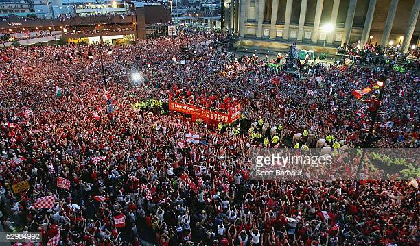 Captain Steven Gerrard holds the trophy aloft as the Liverpool team ride on an open top bus through a mass of fans as they arrive at St George's Hall...