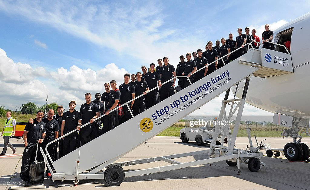 Captain Steven Gerrard of Liverpool (top right) and CEO of Liverpool Football Club Ian Ayre (second top right) pose with the rest of the Liverpool FC team before boarding the plane ahead of the club's pre-season tour of the USA at Liverpool John Lennon Airport on July 20, 2014 in Liverpool, England.