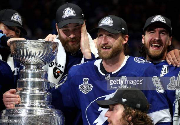 Captain Steven Stamkos of the Tampa Bay Lightning smiles with teammates Pat Maroon, Victor Hedman and Ryan McDonagh with Stamkos' arm around the...
