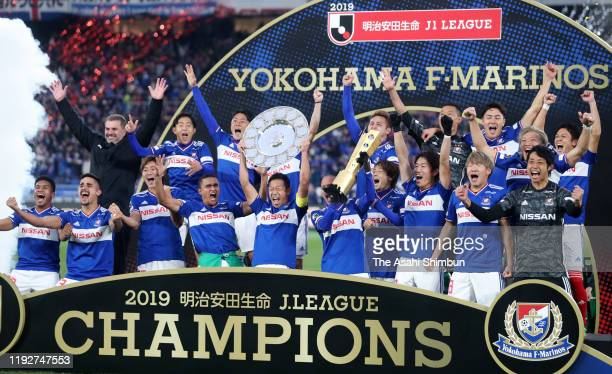 Captain Takuya Kida of Yokohama F.Marinos lifts the trophy at the ceremony as they celebrates the season champions after the J.League J1 match...
