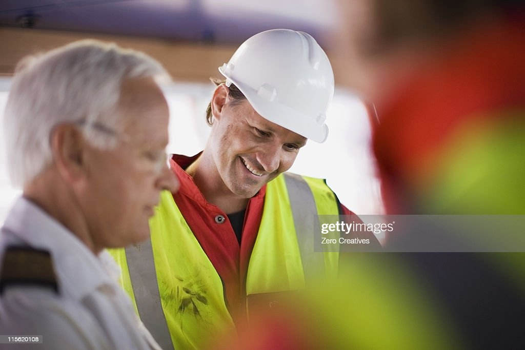 Captain talking to workers : Stock Photo