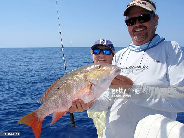 Captain Ted Lund right holds up an African pompano caught on a 100footdeep rock pile out in the Gulf of Mexico by captain Linda Ann Luizza using...