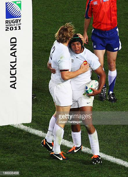 Captain Thierry Dusautoir of France celebrates with teammate Aurelien Rougerie after he scores their first try during the 2011 IRB Rugby World Cup...