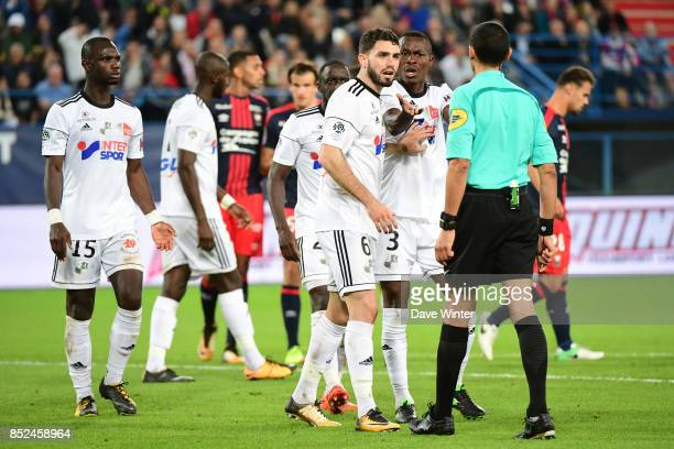 Captain Thomas Monconduit and Khaled Adenon of Amiens argue after referee Hakim Ben El Hadj awards a penalty against them during the Ligue 1 match...