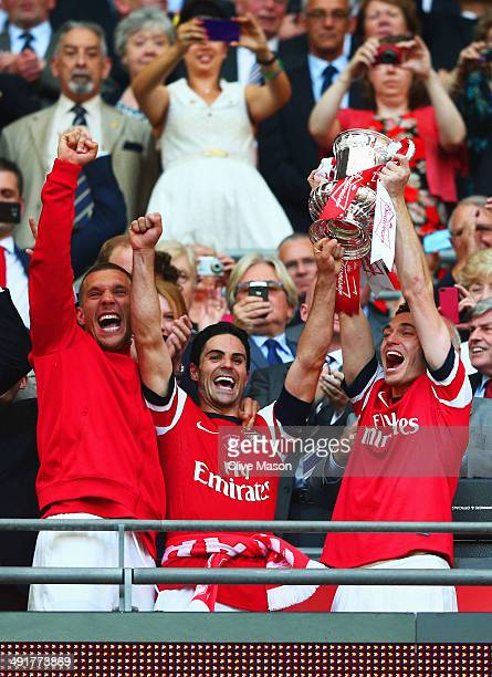 Captain Thomas Vermaelen of Arsenal lifts the trophy in celebration alongside Lukas Podolski and Mikel Arteta after the FA Cup with Budweiser Final...
