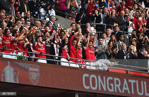 Captain Thomas Vermaelen of Arsenal lifts the trophy in celebration alongside team mates after the FA Cup with Budweiser Final match between Arsenal...