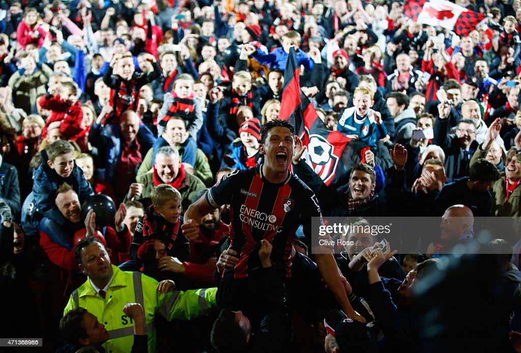 Captain Tommy Elphick of Bournemouth celebrates victory as fans invade the pitch after the Sky Bet Championship match between AFC Bournemouth and Bolton Wanderers at Goldsands Stadium on April 27, 2015 in Bournemouth, England. Bournemouth's 3-0 victory puts them on the brink of promotion to the Barclays Premier League.