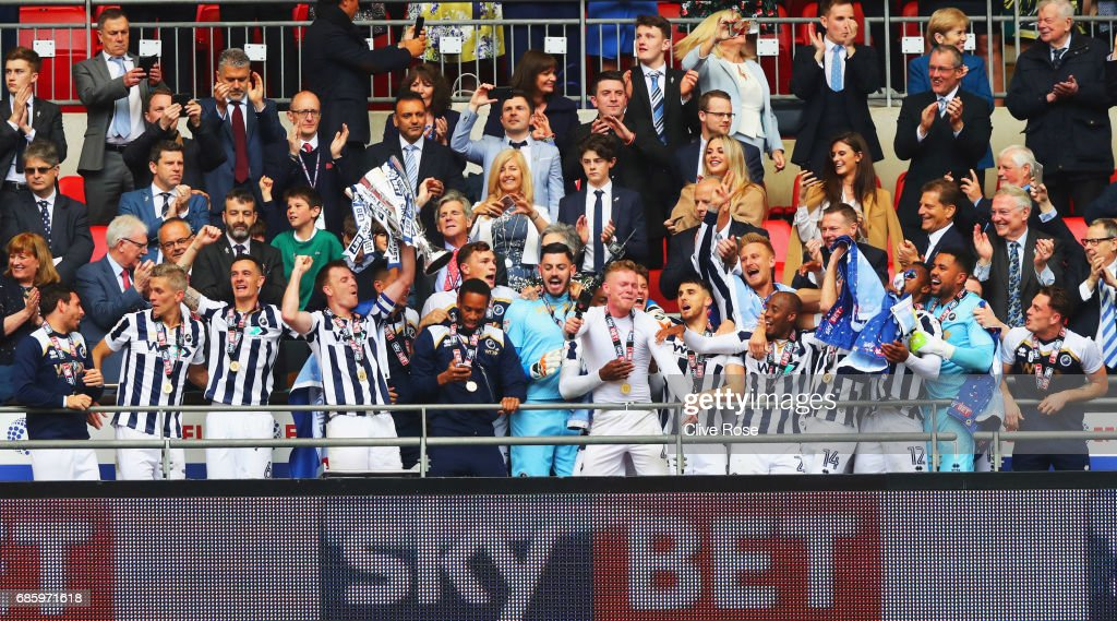 Captain Tony Craig of Millwall (4L) lifts the trophy as he celebrates victory and promotion with team mates after the Sky Bet League One Playoff Final between Bradford City and Millwall at Wembley Stadium on May 20, 2017 in London, England.
