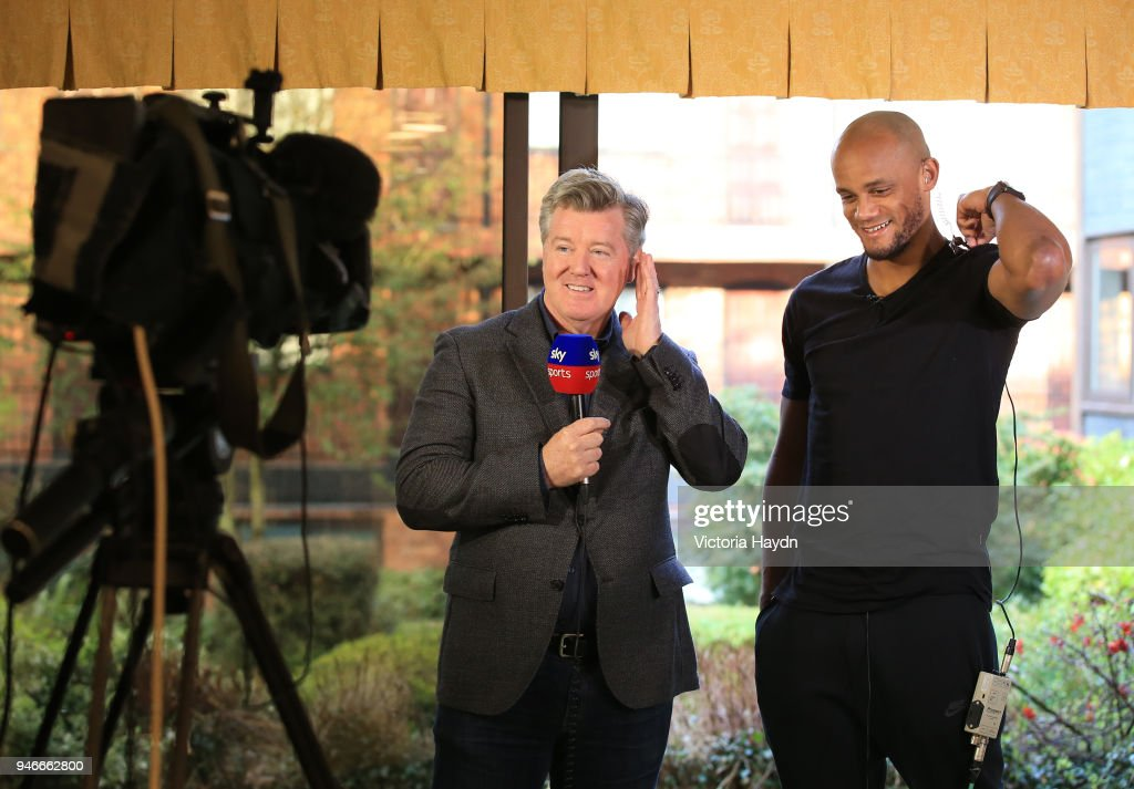 Captain Vincent Kompany (R) of Manchester City celebrates his team Manchester City winning The 2017/18 Premier League during an interview at The Marriott Hotel on April 15, 2018 in Manchester, England.