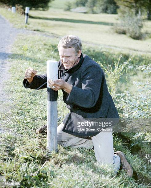 Captain Virgil Hilts played by American actor Steve McQueen sets a wire to dismount a motorcyclist in 'The Great Escape' directed by John Sturges 1963