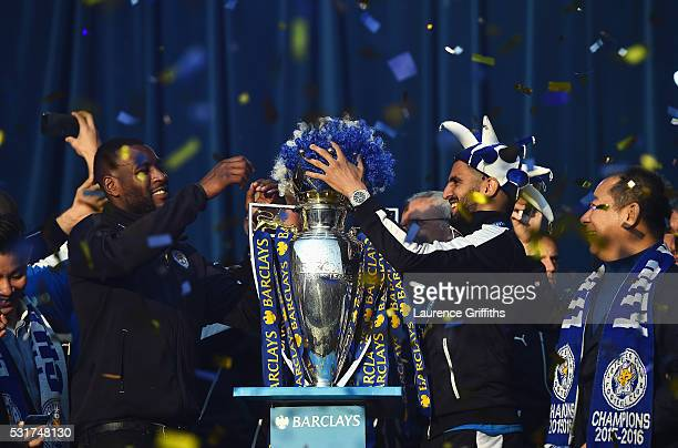 Captain Wes Morgan and Riyad Mahrez of Leicester City place a wig on the trophy during the Leicester City Barclays Premier League winners bus parade...