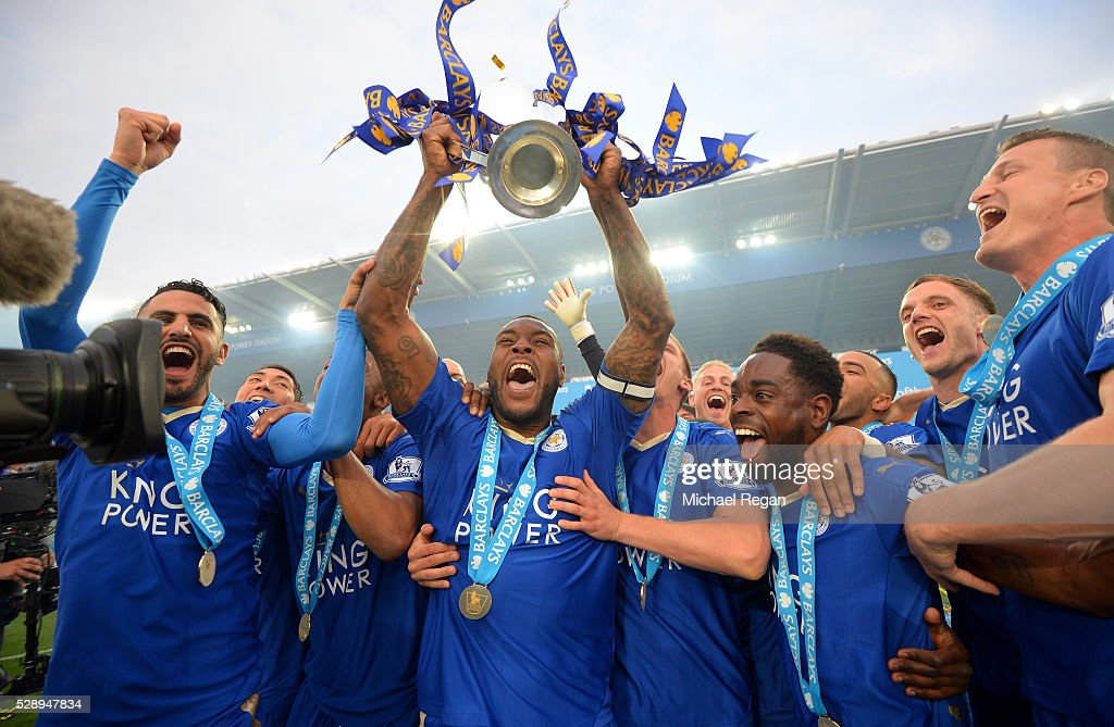 Captain Wes Morgan of Leicester City lifts the Premier League Trophy as players celebrate the season champions after the Barclays Premier League match between Leicester City and Everton at The King Power Stadium on May 7, 2016 in Leicester, United Kingdom.