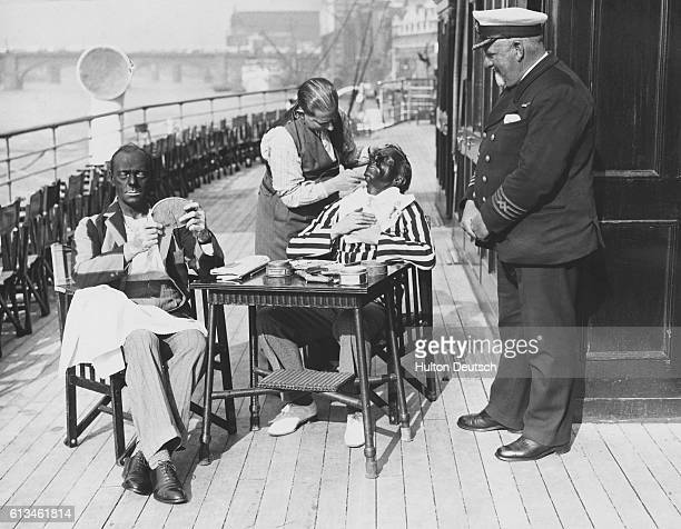 Captain William Grant Braithwaite of the Royal Eagle pleasure steamer watches two actors being made up A film is being shot on board the Captain's...