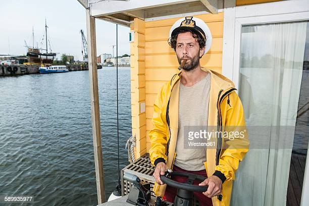 captain with cigar steering hpuse boat - sailor hat stock pictures, royalty-free photos & images