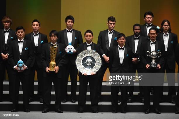 Captain Yu Kobayashi of Kawasaki Frontale holds the JLeague J1 Champions Trophy by JLeague Chairman Mitsuru Murai during the 2017 JLeague Awards at...