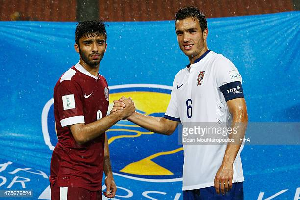 Captains Ahmad Moein of Qatar and Tomas Podstawski of Portugal shake hands in front of the Handshake for Peace flag after the FIFA U20 World Cup New...