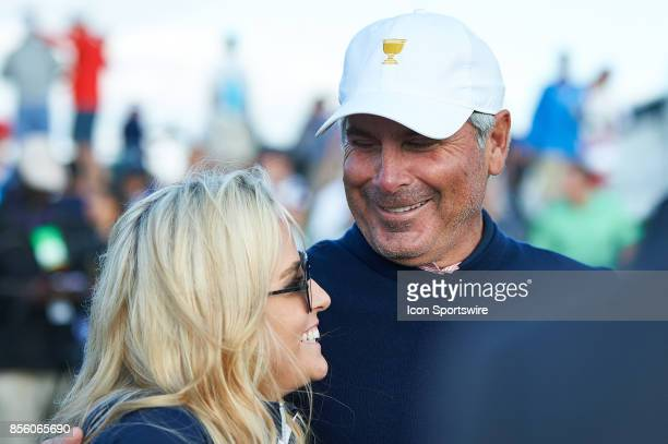 Captain's Assistant Fred Couples of the American Team and Phil Mickelson's wife Amy Mickelson smile on the18th green during the second round of the...