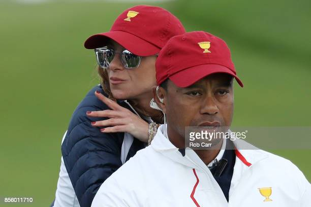 Captain's assistant Tiger Woods of the US Team and Erica Herman lok on during Saturday fourball matches of the Presidents Cup at Liberty National...