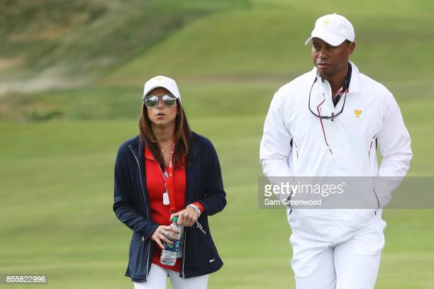 Captain's assistant Tiger Woods of the US Team and Erica Herman look on during Friday fourball matches of the Presidents Cup at Liberty National Golf...