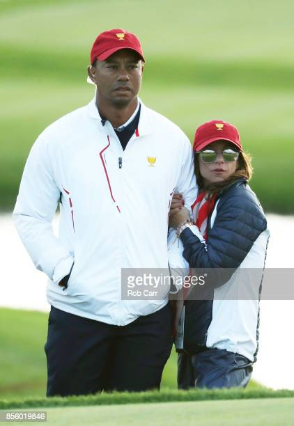 Captain's assistant Tiger Woods of the US Team and Erica Herman look on during Saturday fourball matches of the Presidents Cup at Liberty National...