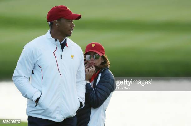 Captain's assistant Tiger Woods of the U.S. Team and Erica Herman look on during Saturday four-ball matches of the Presidents Cup at Liberty National...