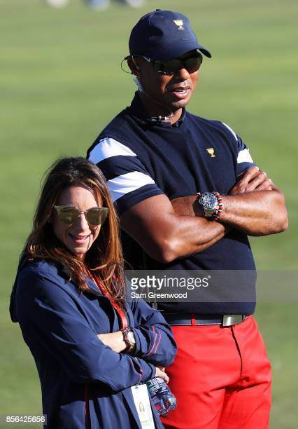 Captain's assistant Tiger Woods of the US Team and Erica Herman look on during Sunday singles matches of the Presidents Cup at Liberty National Golf...