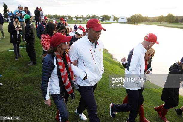 Captain's assistant Tiger Woods of the US Team and Erica Herman walk during Saturday fourball matches of the Presidents Cup at Liberty National Golf...