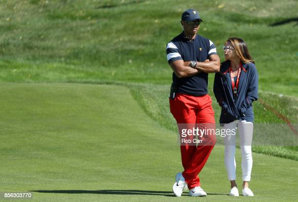 Captain's assistant Tiger Woods of the U.S. Team and Erica Herman walk on the first hole during Sunday singles matches of the Presidents Cup at...