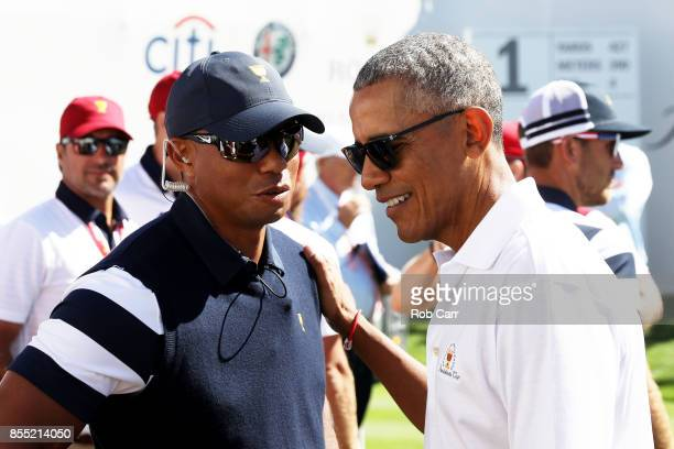 Captain's assistant Tiger Woods of the US Team speaks to former US President Barack Obama on the first tee during Thursday foursome matches of the...