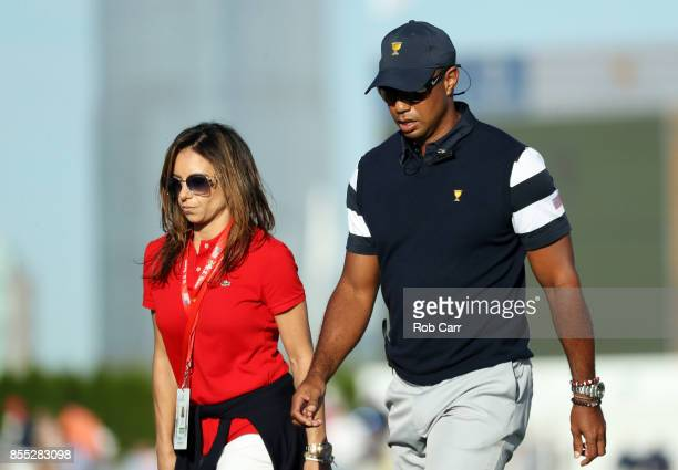 Captain's assistant Tiger Woods of the U.S. Team walks with Erica Herman during Thursday foursome matches of the Presidents Cup at Liberty National...