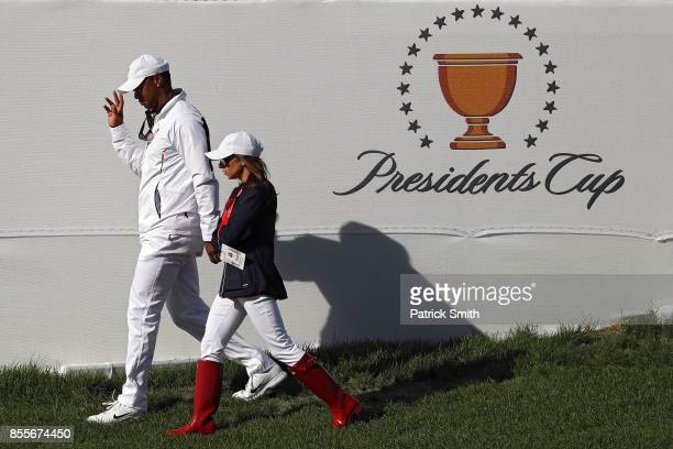 Captain's assistant Tiger Woods of the US Team walks with Erica Herman during Friday fourball matches of the Presidents Cup at Liberty National Golf...