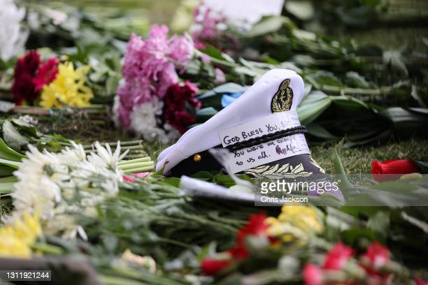 Captain's cap with message of condolence on flowers left outside of Windsor Castle on April 11, 2021 in Windsor, England. The Queen announced the...