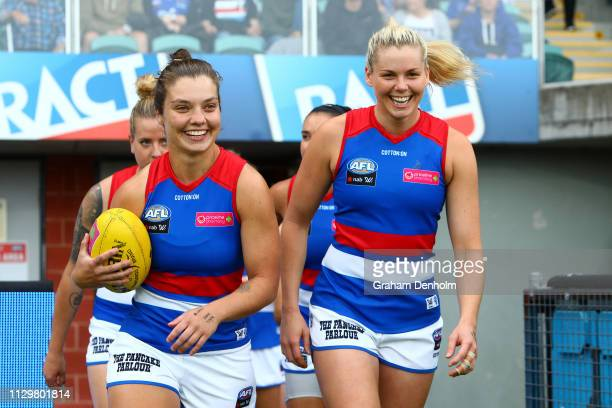 Captains Ellie Blackburn and Katie Brennan of the Bulldogs lead their team onto the field during the round three AFLW match between the North...