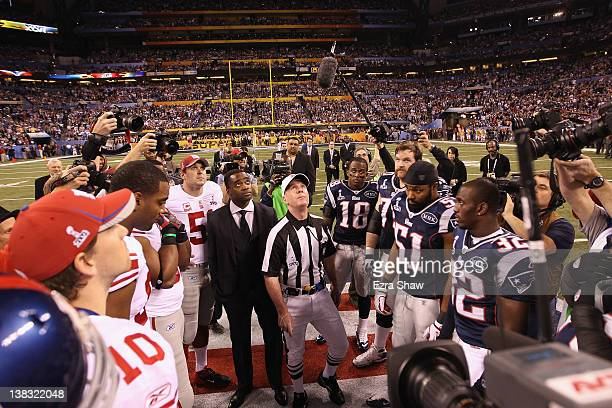 Captains from The New York Giants and the New England Patriots look on as referee John Parry looks up at the coin toss during Super Bowl XLVI at...