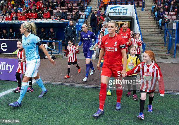 Captains Gemma Bonner of Liverpool Ladies and Steph Houghton of Manchester City Women lead their teams out onto the pitch at the start of the...