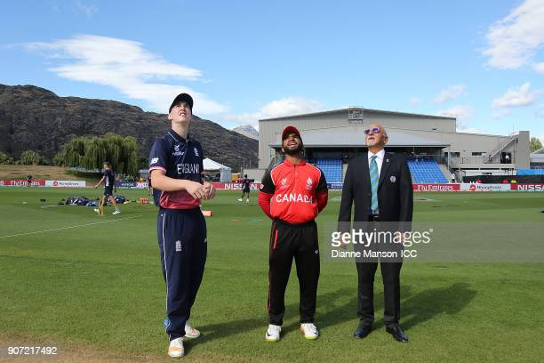 Captains Harry Brook of England Arslan Khan of Canada and ICC Match Referee Devdas Govindjee take part in the coin toss ahead of the ICC U19 Cricket...