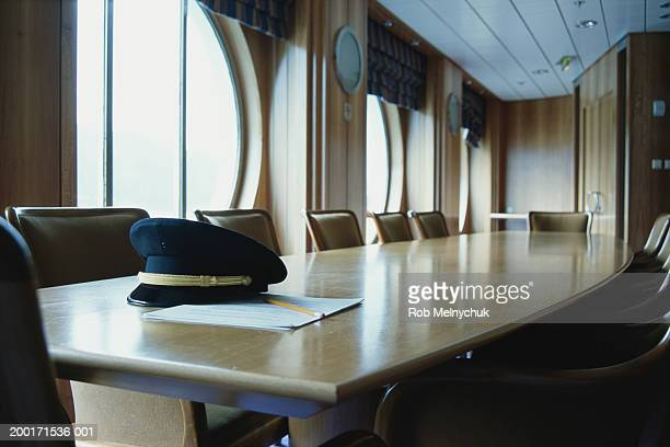 captain's hat on boardroom table - sailor hat stock pictures, royalty-free photos & images
