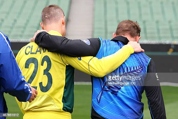 Captains Michael Clarke of Australia and Brendon McCullum of New Zealand walk off arm in arm after posing with the World Cup trophy during the 2015...