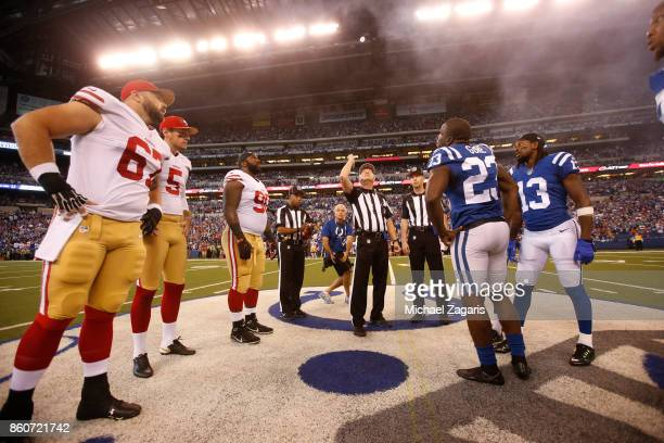 Captains of the San Francisco 49ers and the Indianapolis Colts meet at midfield for the coin toss prior to the game at Lucas Oil Stadium on October 8...