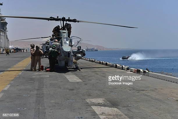 Captains perform pre-flight checks on an AH-1W Super Cobra.