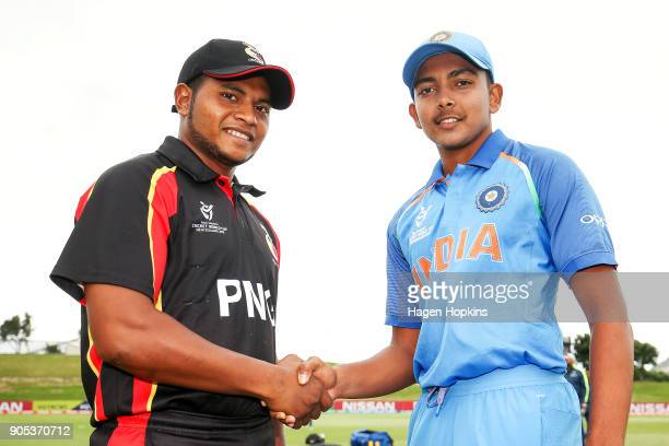 Captains Prithvi Shaw of India and Vagi Karaho of Papua New Guinea shake hands after the coin toss during the ICC U19 Cricket World Cup match between...