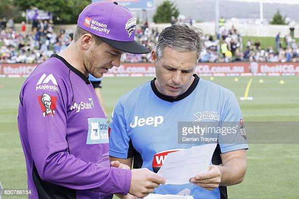 Captains Tim Payne of the Hobart Hurricanes and Brad Hodge of the Adelaide Stikers swap their team sheets before the Big Bash League match between...