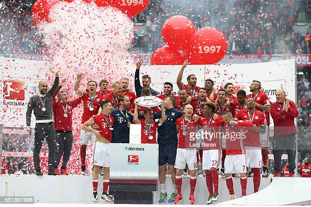 Captian Philipp Lahm of Bayern Muenchen lifts the Meisterschale as players and staffs celebrate the Bundesliga champions after the Bundesliga match...