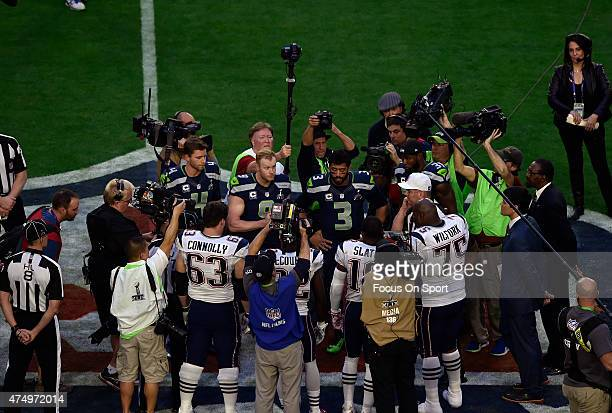 Captins for the New England Patriots and Seattle Seahawks stand for the coin toss prior to the start of Super Bowl XLIX February 1 2015 at the...