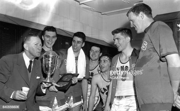 "Kansas coach Dr. Forrest C. """"Phog"""" Allen kisses the national championship trophy following his team's 80-63 victory over St. John's at the Men's..."