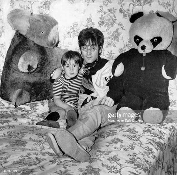 Caption reads 'Even in this homely setting you will recognise father immediately as Beatle John Lennon 27 Flanked by a couple of giant toys he is...